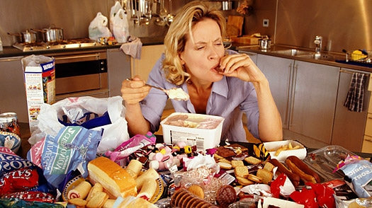 woman eating at table covered with food